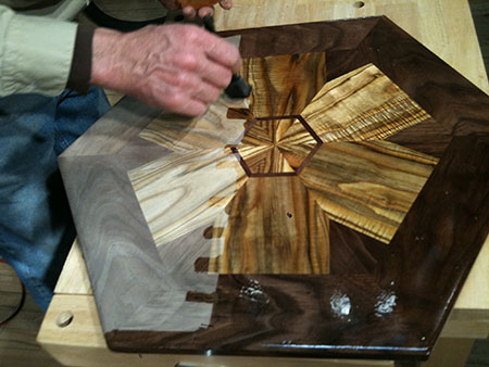 Thomas Schrunk applying finish to the table. Photo: Mark Neuzil.