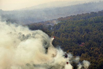 Texas National Guard UH-60 Blackhawk helicopters release water onto the Bastrop County Complex Fire in September 2011.