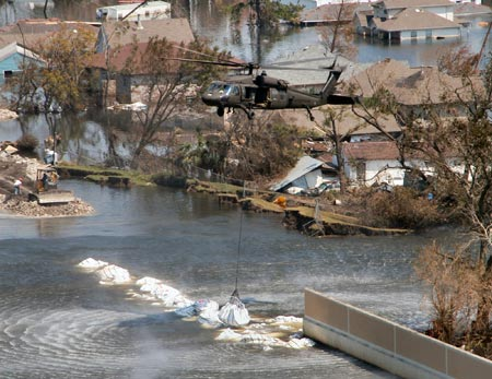 A Texas Army National Guard Blackhawk deposits a 6,000 pound-plus bag of sand and gravel on-target, Sunday, September 4, 2005, as work progressed to close the breach in the 17th Street Canal in New Orleans post-Katrina.