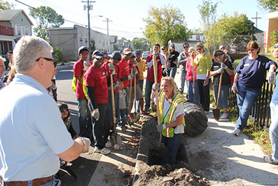 New Jersey Tree Foundation Director Lisa Simms demonstrates tree planting for Bank of America volunteers in Asbury Park, N.J.