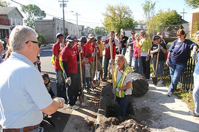 New Jersey Tree Foundation Director Lisa Simms demonstrates tree planting for Bank of America volunteers in Asbury Park, N.J.