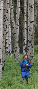 Author Tyler Williams standing in an aspen grove