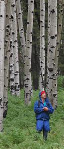 Author Tyler Williams standing in an aspen grove