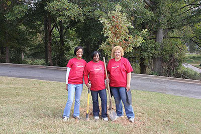 Bank of America volunteers stand with a tree they have planted as part of a Community ReLeaf planting event at Price Middle School in Atlanta.