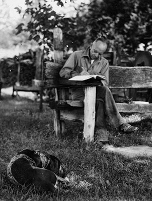 Aldo Leopold writing at his shack with his dog, Flick.