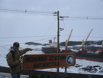 A geocacher finding a virtual cache and McMurdo Station, Antarctica.