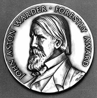 The John Aston Warder award, featuring his likeness.