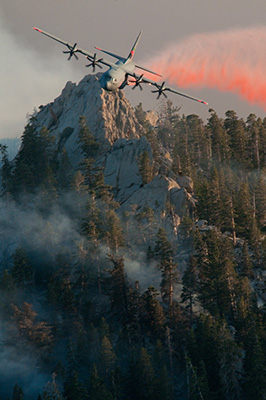 A National Guard aircraft rops retardant over trees as part of the response to the 2013 Mountain Fire