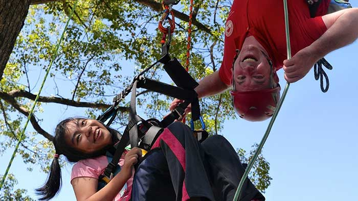 John Gathright helps a young tree climber discover her potential.