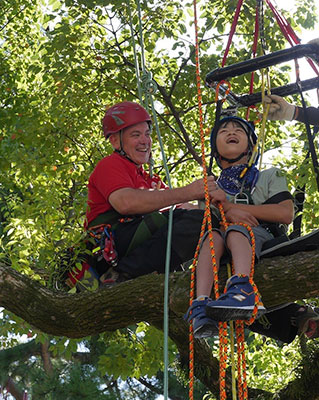 John Gathright and a young tree climber reach a treetop
