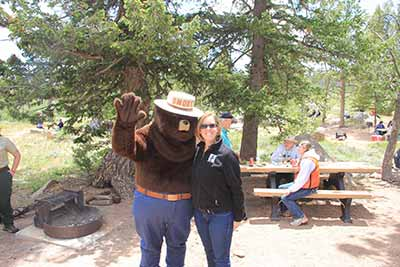 Jami Westerhold poses with Smokey Bear at a volunteer event in summer 2014.