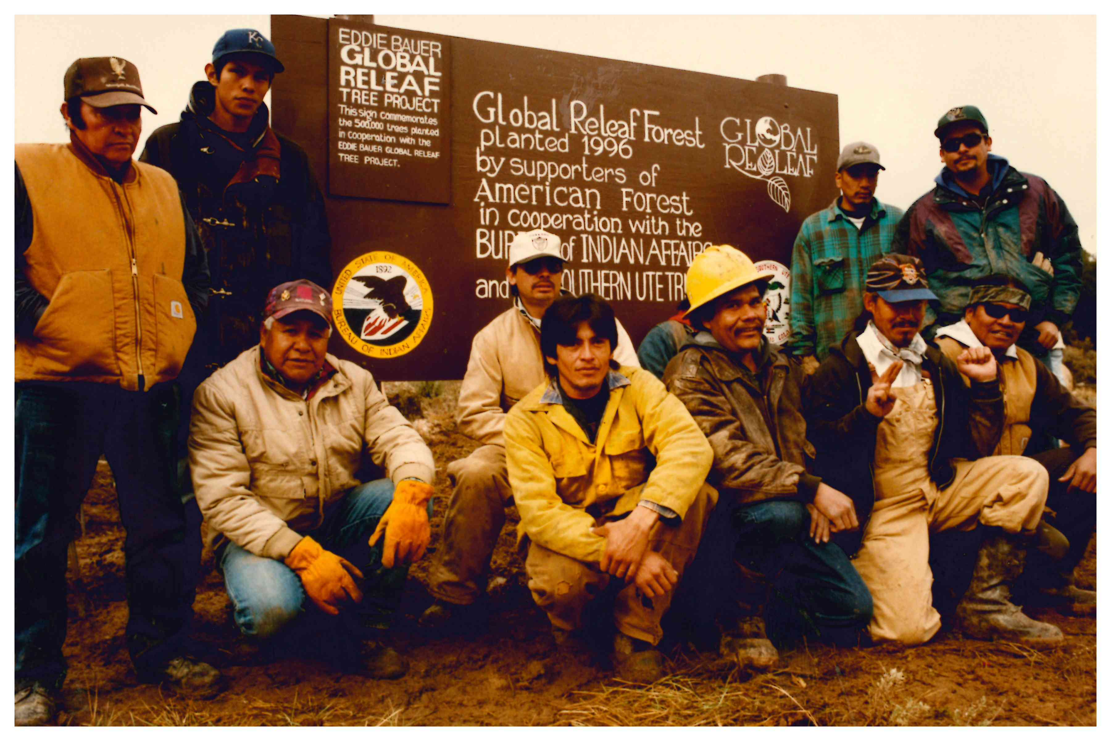 Ute men posing in front of commemorative Global ReLeaf sign
