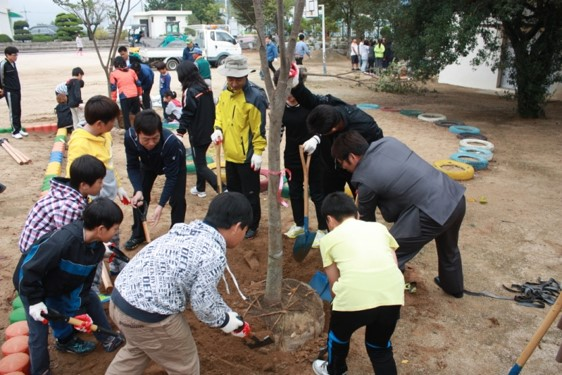 Students and teachers helping plant trees at HaCheon Elementary School in Changwon, South Korea.