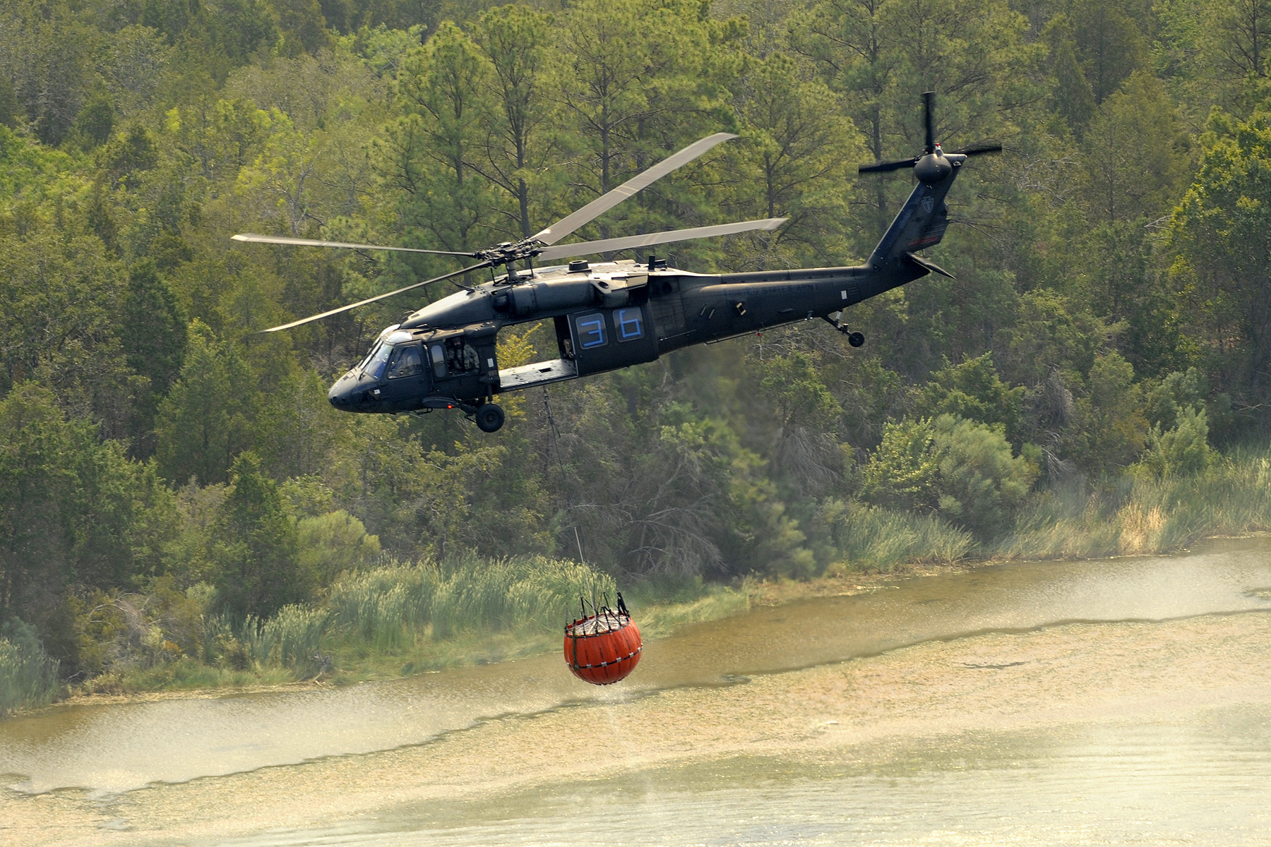 A Texas National Guard Black Hawk helicopter heads back to battle the blaze after it refills its Bambi Bucket.