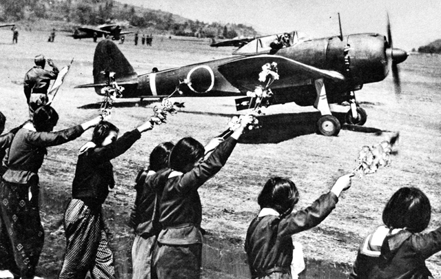 Chiran high school girls are waving farewell with cherry blossom branches to a taking-off kamikaze pilot.