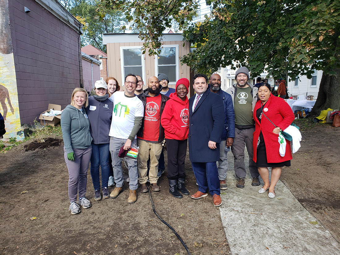 Mass. State Senator Nick Collins (navy coat) and Representative Liz Miranda (red coat) joined H.E.R.O. Hope Garden founder Judith Foster (red hat) and the team to install the new garden in Dorchester.