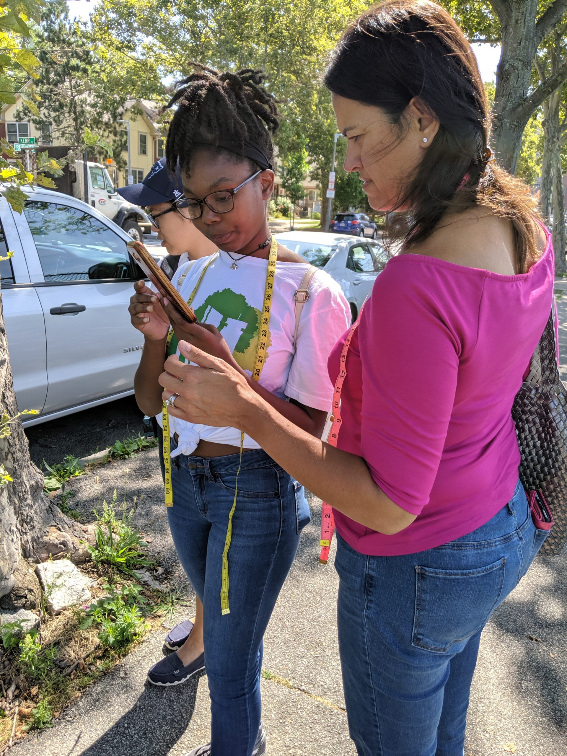 Teen Urban Tree Corps member Maya Hall (left) shows Boston City Councilor Anissa Essaibi George the process for recording tree inventory data.