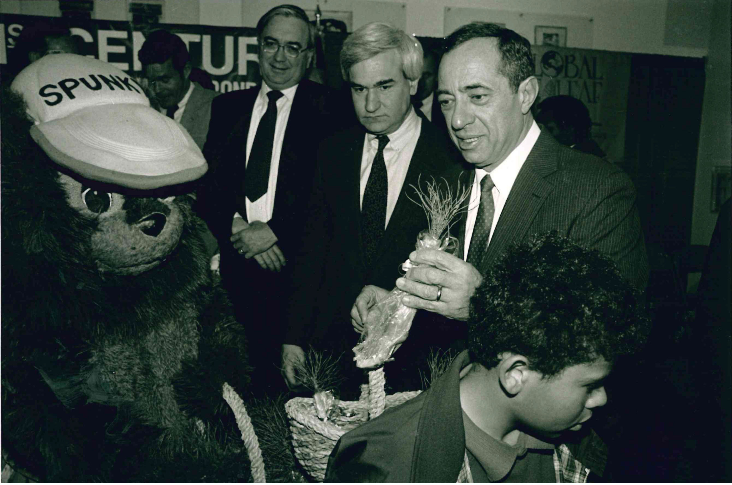 American Forests executive vice president at the time stands with the New York state department of environmental conservation commissioner as Governor Mario Cuomo and our (since retired) mascot Spunky hand out seedlings to school children in 1990.
