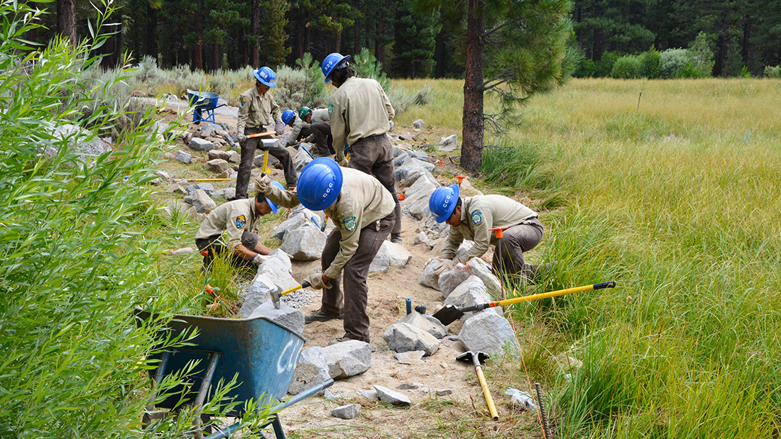 Tahoe Center California Conservation Corps members shape rocks to create the siding for an ADA accessible trail at Grover Hot Springs State Park in Markleeville, Calif.