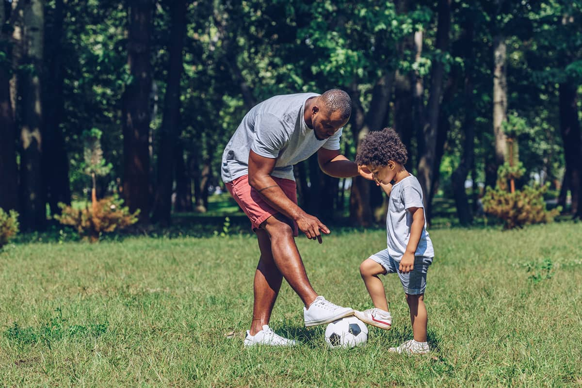 A father teaches his young son to play soccer in a park surrounded by trees.