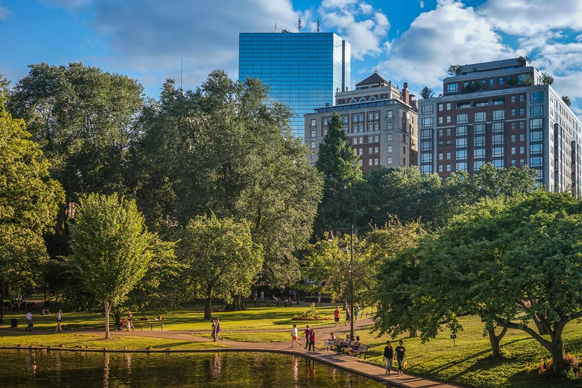 People walk in a city park with the Boston skyline in the background.