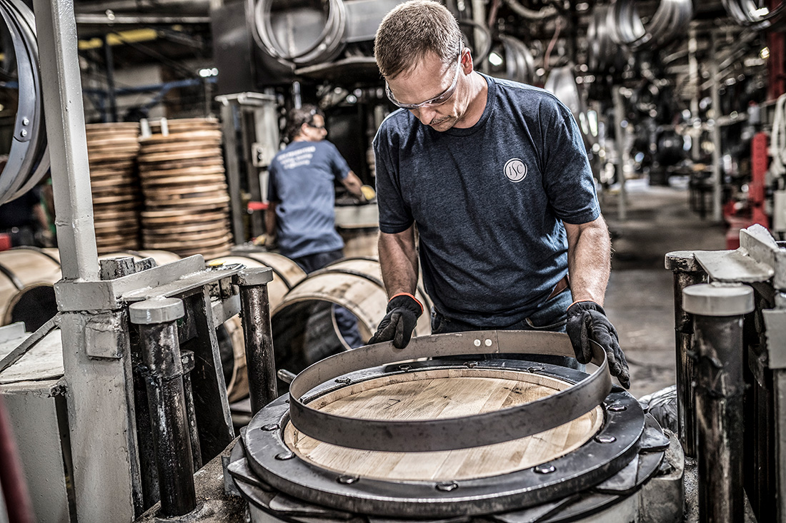 Securing top and bottom barrel heads is one of the last touches in barrel production. Here, an employee at Kentucky Cooperage is placing the head hoop on a barrel.