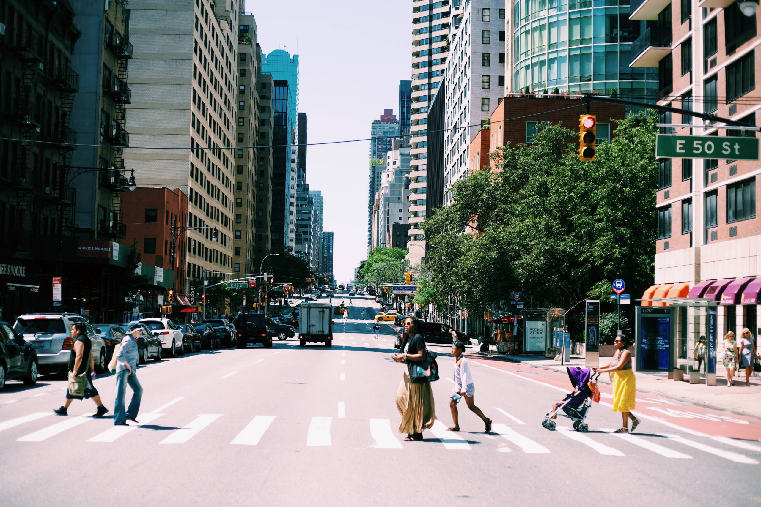 People cross the street in a city with little tree canopy.